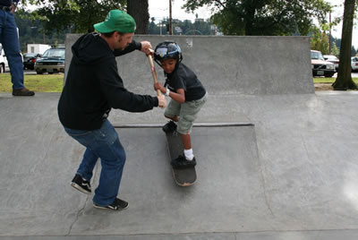 skateboard instructor helping kid drop in
