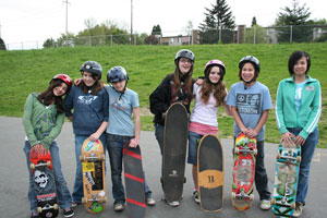 female skateboards hanging out with their boards in hand